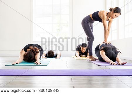 Asian sporty people learning Yoga class in fitness club. Instructor coaching and adjust correct pose on child pose to student. Yoga Practice Work out fitness healthy lifestyle concept.