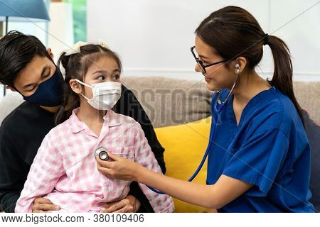 Asian female doctor use stethoscope to listen heartbeat of little girl child sit with her father in living room while doctor visit at home. Home health care delivery and doctor visiting concept.