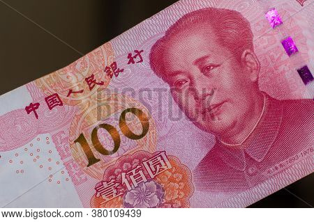 Currency Of The China - One Red Hundred Renminbi Or Yuan Notes Spread Out On A Brown Background. Mon