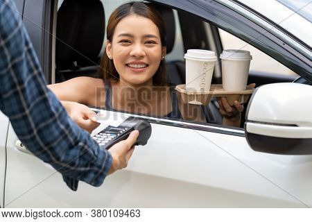 Asian woman customer make mobile payment contactless technology on drive thru food service restaurant while picking up coffee. Drive through is new normal popular after coronavirus covid-19 pandemic.