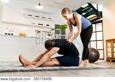 White caucasian man learning yoga at home. Female instructor or trainer coaching and adjust correct pose to student. Workout healthy lifestyle and Yoga health delivery concept.