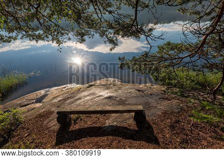 A Simple Wooden Bench Stands On The Stone Shore Of The Lake. There Is A Shadow From The Bench And Pi