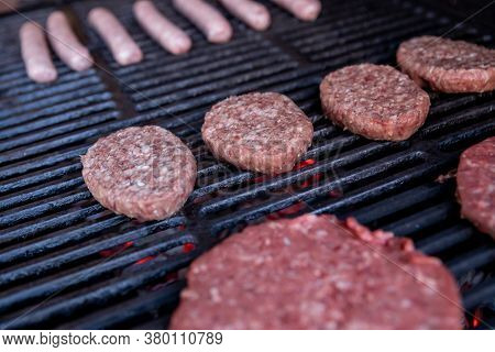 Sausages And Burgers Cooking On Grill.meat Cooking On A Barbecue Grill, Selective Focus.burger Meat