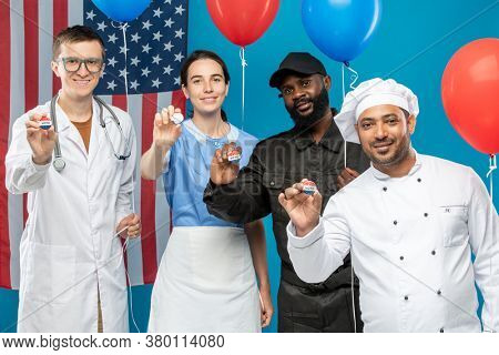 Multi-cultural group of young contemporary doctor, maid, chef and security guard showing vote insignias against American flag