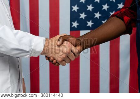 Contemporary clinician in whitecoat and young African repairman shaking hands in front of camera against stars-and-stripes flag