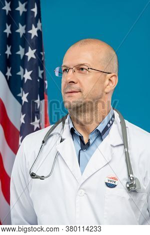 Contemporary bald clinician with vote insignia on whitecoat standing in front of camera against stars-and-stripes and blue background