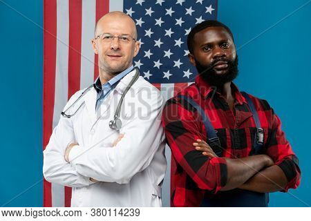 Mature bald clinician and young African repairman crossing arms on chest while looking at you against stars-and-stripes flag