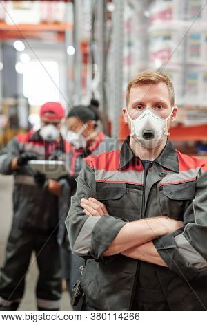 Young blond man in workwear and protective respirator crossing his arms by chest while standing in front of camera in warehouse