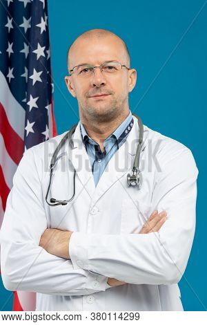 Mature bald clinician in whitecoat crossing arms on chest while looking at you against stars-and-stripes flag and blue background