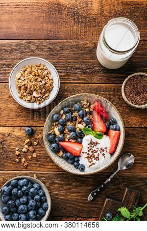 Granola Bowl With Blueberries, Strawberries And Greek Yogurt On A Rustic Wooden Table Background. To