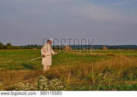 An Senior Muslim Man In An Embroidered Skullcap And White Traditional Clothes Mows Hand-scythe Grass