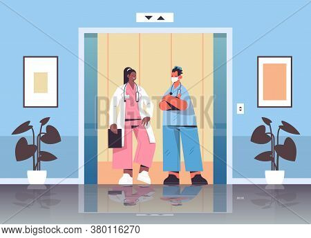 Mix Race Medical Workers Discussing During Meeting In Hospital Elevator Healthcare Medicine Concept