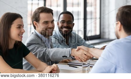 Smiling Business People Shaking Hands, Sitting At Table In Boardroom
