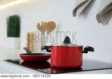 Red Pot And Frying Pan On Stove In Kitchen
