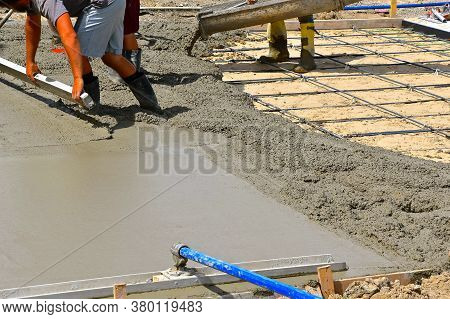 A Team Of Concrete Workers Are Screeding, Troweling And Pouring Wet Mud On A New Driveway Site.