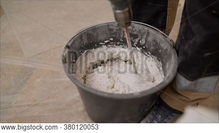 Mix The Mixture In A Black Bucket. Worker Mixes A Solution In A Black Bucket. A Man Mixes A White Mi
