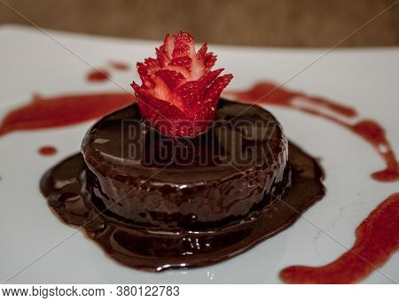 Close-up On Chocolate Fudge Covered With Chocolate Sauce And Decorated With Sculptured Strawberry On