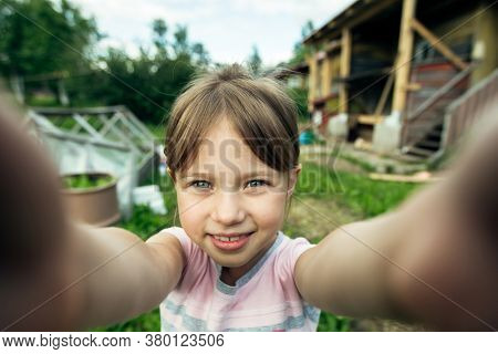 Little cute girl funny taking a selfie out in the viilage house.