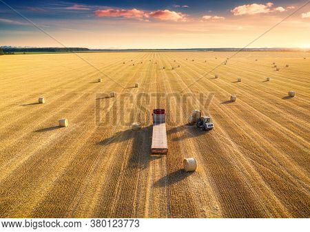 Aerial View Of Truck With Hay Bales. Agricultural Machinery. Chamfered Field And Hay Stacks After Ha