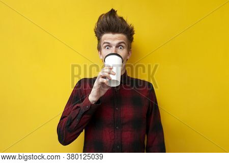 Young Shocked Guy Drinks Invigorating Coffee And Is Surprised At A Yellow Isolated Background, A Man