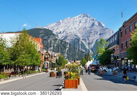 Banff, Canada - July 29, 2020: Tourists Walk Along Banff Avenue In Banff National Park With Cascade