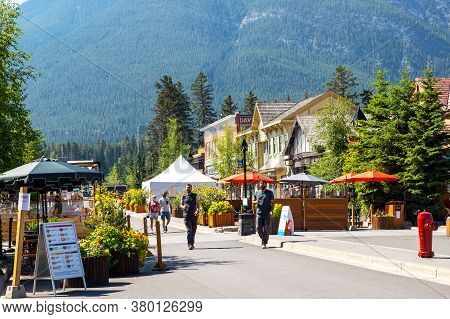 Banff, Canada - July 29, 2020: Tourists Walk Along Banff Avenue In Banff National Park. The Street W