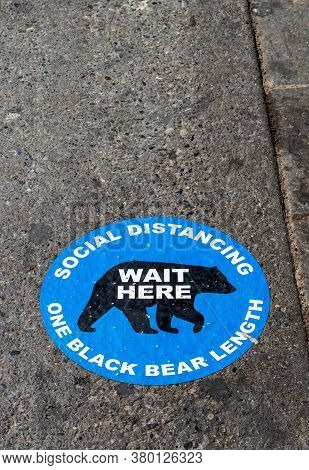 Banff, Canada - July 29, 2020: Social Distancing Road Pavement Sticker To Help Visitors At Popular B