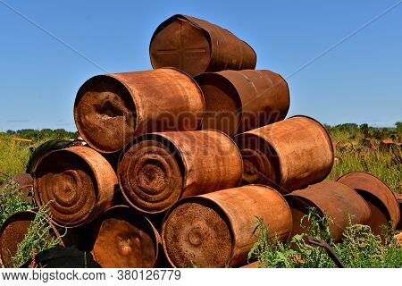 A Pile Of Old Rusty Canisters For Carrying Liquids Are Piled Up In A Salvage Yard.
