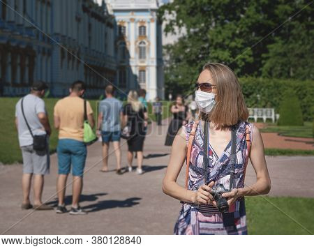 Female Tourist In A Medical Mask On The Street. Safety In A Public Place While Epidemic Of Covid-19.