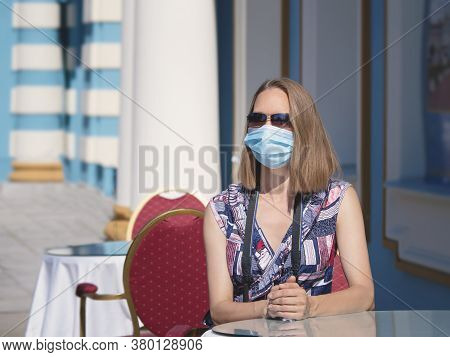 Female Tourist In A Medical Mask Is Sitting At A Cafe Table On The Street. Safety In A Public Place