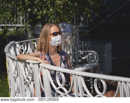 Female Tourist In A Medical Mask Sits On The Street. Safety In A Public Place While Epidemic Of Covi