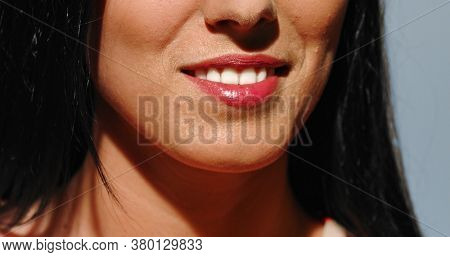Close view of woman teeth smlie with white teeth and red lips.