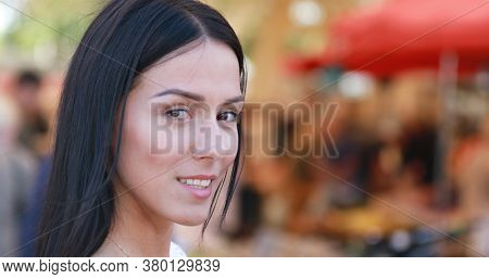 Smilling woman is standing on busy city street looking at camera.