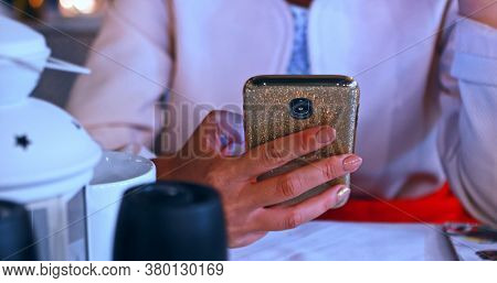 Close view of woman browsing smartphone in cafe. Social media.