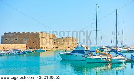 Harbour with boats and yachts by the Koules Fortress in Heraklion on sunny summer day, Crete, Greece