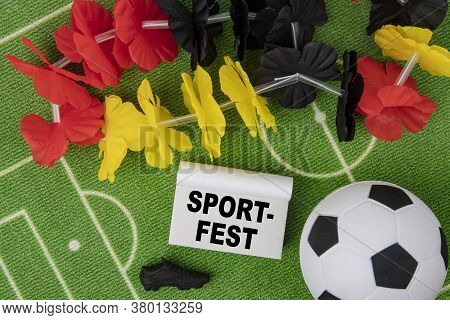 Sport Fest In German Language Means Sport Event. Soccer Ball With Flower Necklace In The Colors Of G