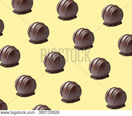 Tasty Chocolate Candies On Pale Yellow Background. Pattern Design