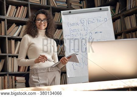 Smiling Female Young Hispanic School Math Teacher, College Tutor Looking At Camera Standing In Class