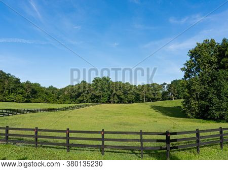 A Rollling Green Field Surrounded By Trees And A Wooden Fence In A Rural Area In Georgia; Landscape