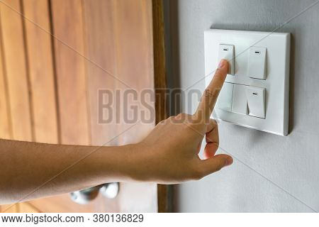 Close Up Of Female Finger Is Turning Off On Lighting Switch Near Wood Door At Home. Power, Energy, S