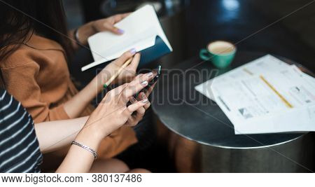 Two Young Asian Woman Working Together And Using Mobile App From Smart Phone  Search Information Fro