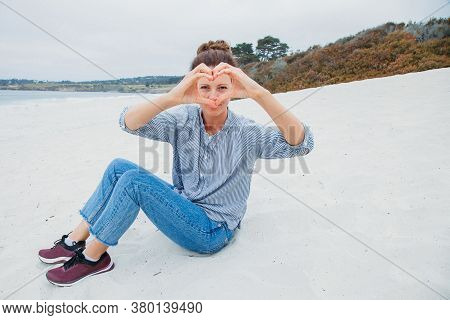 Beautiful Young Woman In Blue Jeans And A Shirt Have Fun Outdoors In Cloudy Weather. Pretty Young Wo