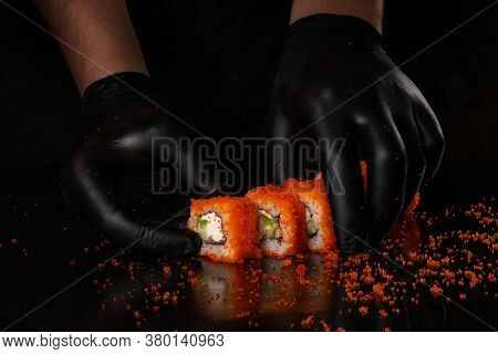 Process of making California roll sushi with red masago caviar by hand in black gloves on black background