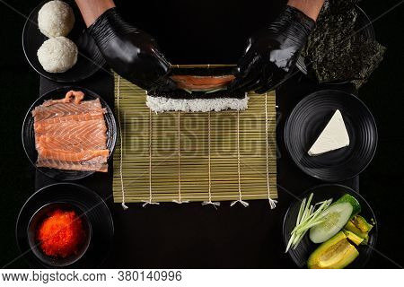 Process of making  California roll sushi by hands in black gloves on black background framed by plates with ingridients with salmon, cucumber, avocado, cream cheese, red masago caviar