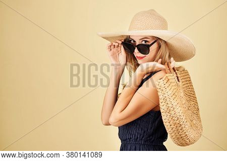 Charming Young Woman With Straw Bag Taking Off Sunglasses And Looking At Camera, Isolated On Yellow