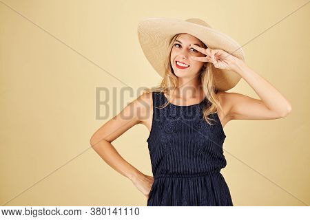 Charming Elegant Young Woman In Straw Hat Making Peace Gesture And Smiling At Camera