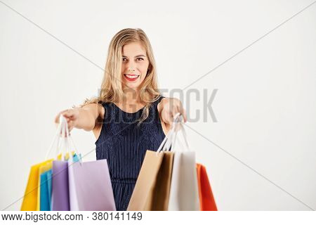 Cheerful Young Woman Outstretching Hands With Shopping Bags, Isolated On White