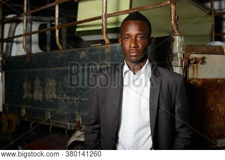 Young African Businessman In Suit Against Old Pickup Truck