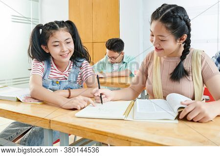 Smiling Asian Teenage Girl Helping Classmate With Doing School Project