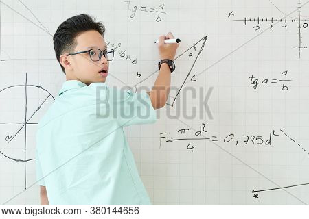 Vietnamese Schoolboy Listening To Advice Of Classmate When Solving Geometry Task And Writing On Whit